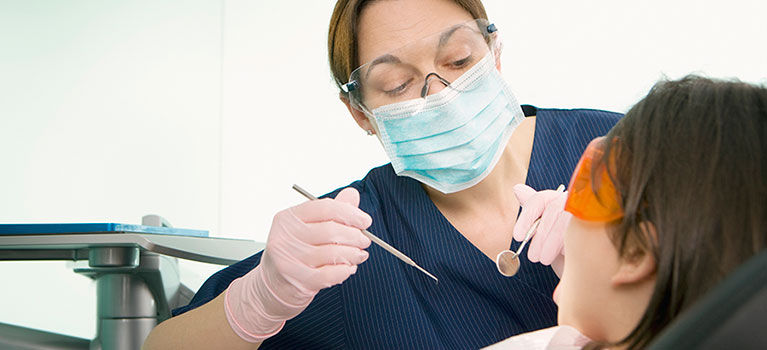 A female dentist treating a patient